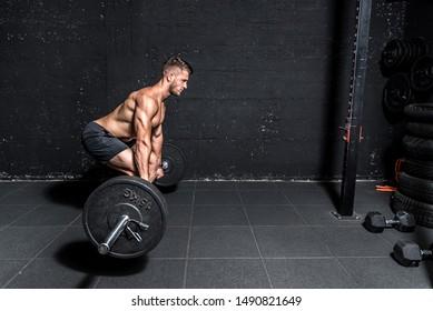 Junge, starke Muskelschwund Mann mit großen Muskeln, die Barbell-Gewicht-Hub-Cross-Training in der Gymnastik dunkle Bild wirkliche Menschen