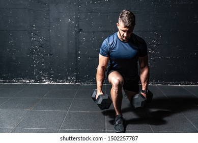 Junge, kräftig fit muskulösen schwitzigen Mann mit großen Muskeln Kraft Cross Training mit Hantel Gewichte im Fitnessraum dunkles Bild mit Schatten echte Menschen