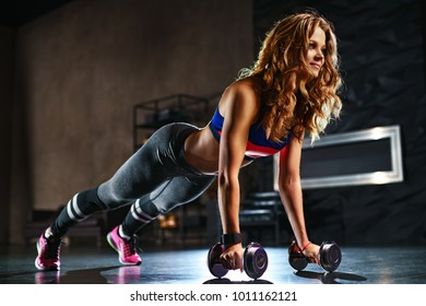 Young strong fitness woman doing push ups with dumbbells in modern hall interior
