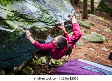Young strong girl climbing on hard boulder outdoor
