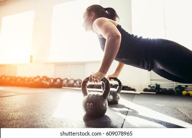 Young strong girl doing push-ups on kettlebells