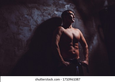 a young strong guy, a karate with a strong naked torso stands against the wall clenched his hands