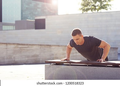 Young and strong guy training outdoor in sportswear. Man in a light of sunset. Sport, health, fitness and athletics.