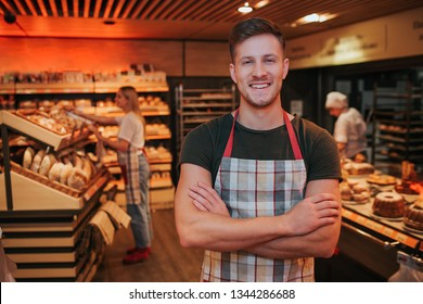 Young strong handsome man stand in grocery store or bakery. He crossed hands and smile. Positive worker. Young woman work behind close to bakery shelf.