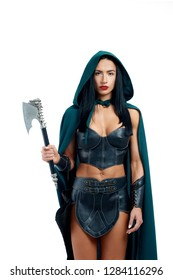 Young and strong lady warrior in leather armor ready for fight. Elegant woman holding axe and posing at camera. Beautiful girl in emerald cloak making cosplay of favourite creature in online games.