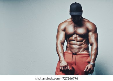 Young strong man bodybuilder posing on white wall background