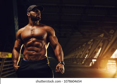 Young strong man bodybuilder standing in urban city interior
