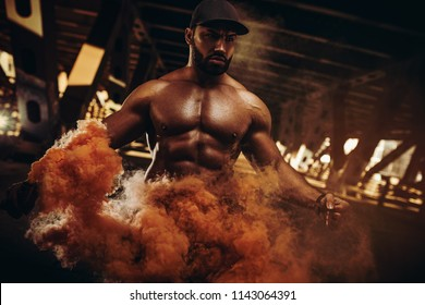 Young strong man bodybuilder standing in urban city dramatic interior with dense red smoke