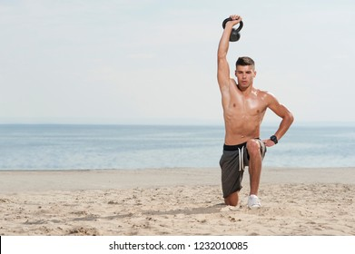 Young strong man doing lunges exercise with kettle bell. Muscular male athlete exercising outdoors at the beach against sky. Cross power training