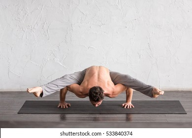 A young strong man doing yoga exercises - handstand. Studio shot over white brick background and black floor