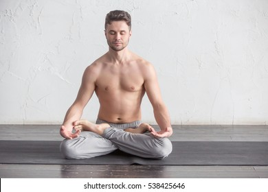 A young strong man doing yoga exercises - lotus pose and meditates with padmasana legs. Studio full length shot over white brick background and black floor, copy space.