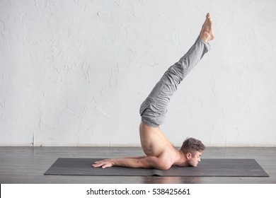 A young strong man doing yoga exercises - handstand. Studio shot over white brick background and black floor.