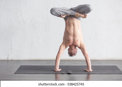 A young strong man doing yoga exercises - Salamba sirsasana, handstand with padmasana legs. Studio full length shot over white brick background and black floor, copy space.