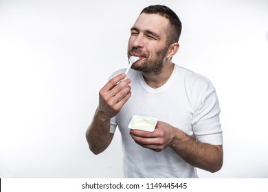 Young and strong man is eating yogurt. He is doing that with pleasure. Isolated on white background.