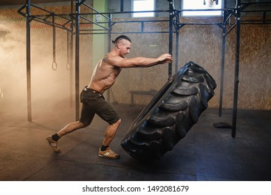 Young strong man with naked torso flipping tire during training in the gym full of smoke.