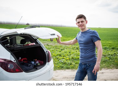 Young strong man near his outdoors car on a road
