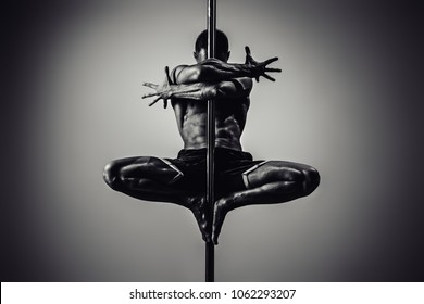 Young strong man pole dancing. Black and white dramatic colors.