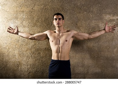 Young strong man posing in studio shot with serene expression and open arms