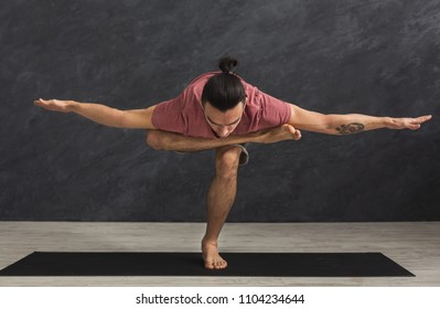 Young strong man practicing yoga, standing in flexible pose on mat in fitness class, making balance exercise, copy space