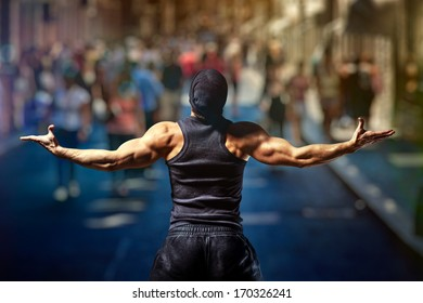 Young strong man standing on street against people.