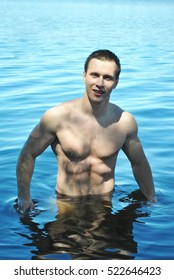 Young strong man in water