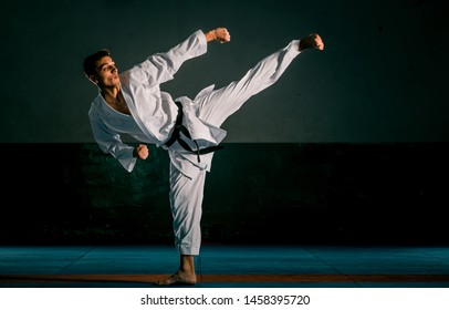 A young strong man in a white kimono for sambo, jiu jitsu and other martial arts with a black belt training in gym, low key, high contrast