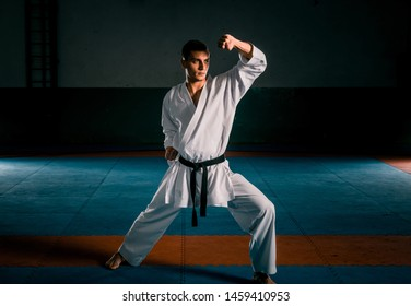 A young strong man in a white kimono for sambo, jiu jitsu and other martial arts with a black belt training in gym