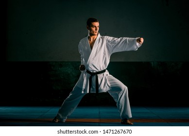 A young strong man in a white kimono for sambo, jiu jitsu and other martial arts with a black belt training in gym, isolated on black