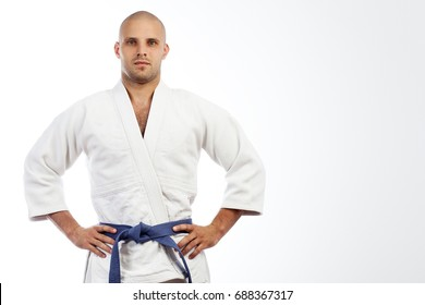 A young strong man in a white kimono for sambo, jiu jitsu and other martial arts with a blue belt posing on white isolated background, hands holding on his belt