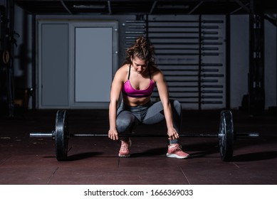 Young strong muscular fit girl with big muscles preparing for hard strength weightlifting or dead lift crossfit workout training with barbell weights in the gym real people exercising