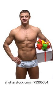 A young strong muscular man with a beautiful gift box and ribbon