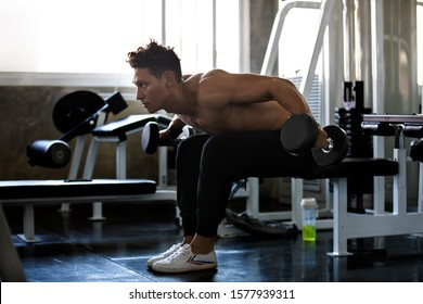 Young strong muscular man with big muscles  focused on weight training with dumbbell hard core workout in the gym.