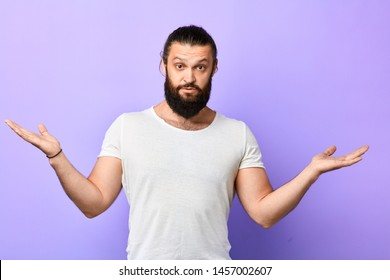 young strong muscular man showing ignorance, shrugging shoulder on a blue background. handsome man in white T-shirt with raised arms exresses doubtfulness.