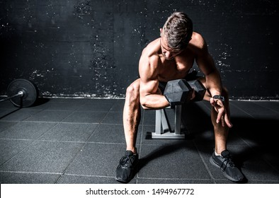 Young strong muscular sweaty fit man biceps muscle workout cross training with heavy dumbbell in the gym dark image with shadows real people
