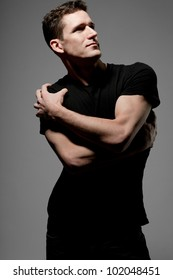 Young strong slim man in black t-shirt posing on gray background.