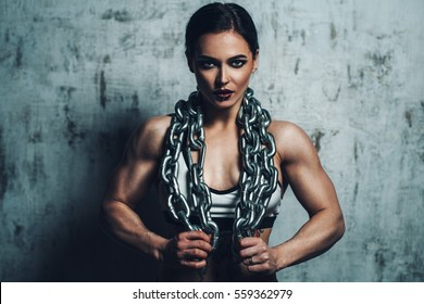 Young strong sports woman with heavy chain and piercings on face. Tattoo on body.
