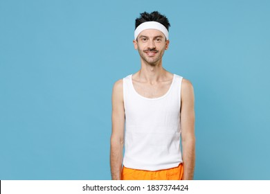Young strong sporty fitness man with thin skinny body sportsman in white headband shirt shorts doing stretching exercising for hands isolated on blue background. Workout gym sport motivation concept