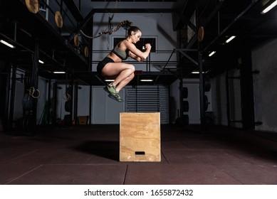 Junge, starke schwatschende Fitnessmuskulatur mit großen Muskeln zu tun Box-Jump Hardcore Cross Training in der Gym selektive Fokusbewegung unscharfe Menschen Sport