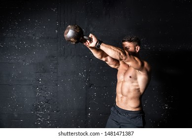 Young strong sweaty focused fit muscular man with big muscles holding heavy kettle bell for swing cross training hard core workout in the gym