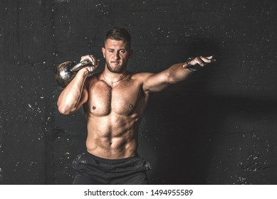 Young strong sweaty focused fit muscular man with big muscles holding heavy kettle bell for training hard core cross workout in the gym real people