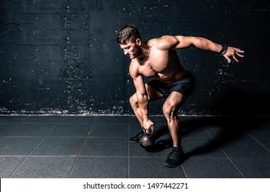 Junge starke, schwitzige, passionierte Muskeln mit großen Muskeln, die schwere Kettlebell für Cross-Swing Training harte Kerntrainings in der Gymnastik realen Menschen