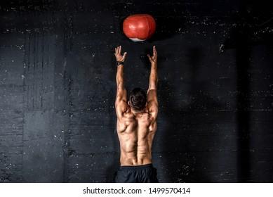 Junge starke schwitzige konzentrierte fit muskulösen Mann mit großen Muskeln werfen MedikBallung auf die Wand für Cross Training harte Kerntrainings im Fitnessraum echte Menschen selektiver Fokus