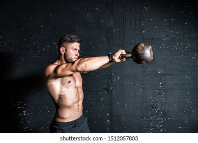 Young strong sweaty focused fit muscular man with big muscles holding heavy kettlebell for swing crossfit training hard core workout in the gym