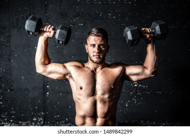 Young strong sweaty man shoulders workout training with two dumbbells in the gym dark image with shadows real people