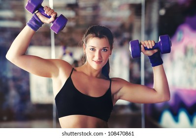 Young strong woman with dumbbells.