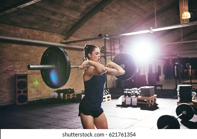 Young strong woman lifting barbell in gym. Horizontal indoors shot