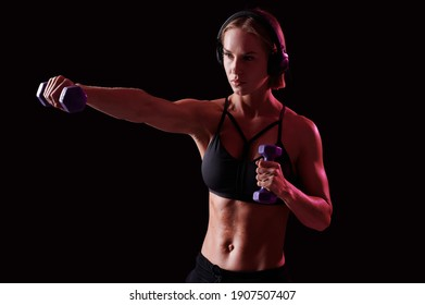 Young strong woman with perfect abdomen and strong arms working out with dumbbells on black background