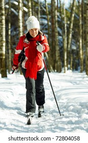 young strong woman is skiing in the forest