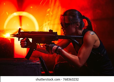 Young strong woman warrior shooting from machine gun in dramatic urban night scene. Tattoo on body.