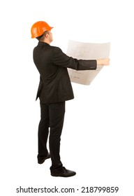 Young structural engineer holding as blueprint unrolled in his hands as he conducts an inspection, full body in suit and hardhat , side view on white